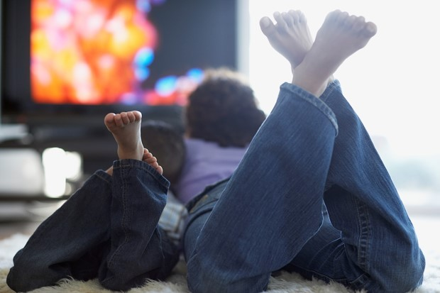 Bild: Mother and Son Watching Television --- Image by © Laura Doss/Corbis